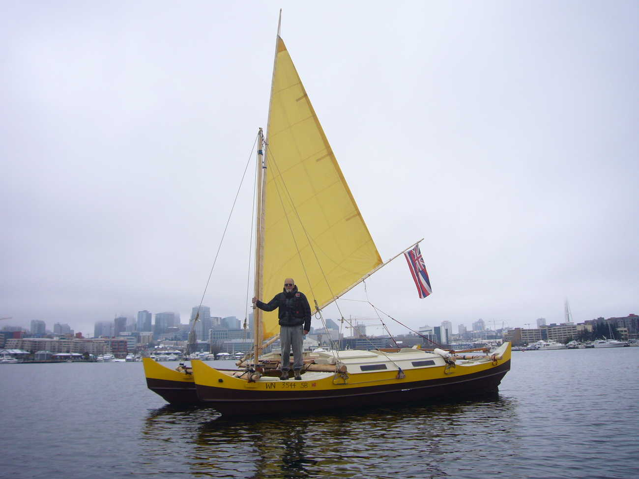 Yellow and black Pahi 26 with a crabclaw sail, one man aboard and a city in the background