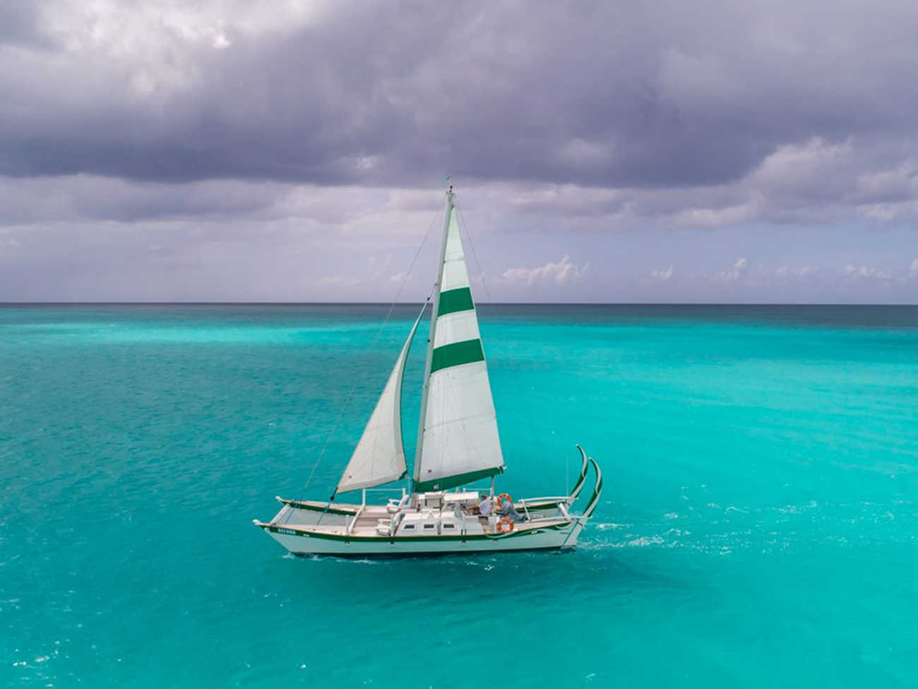 Raka with green and white colours and very high rudders, sailing on a light blue sea, cloudy sky