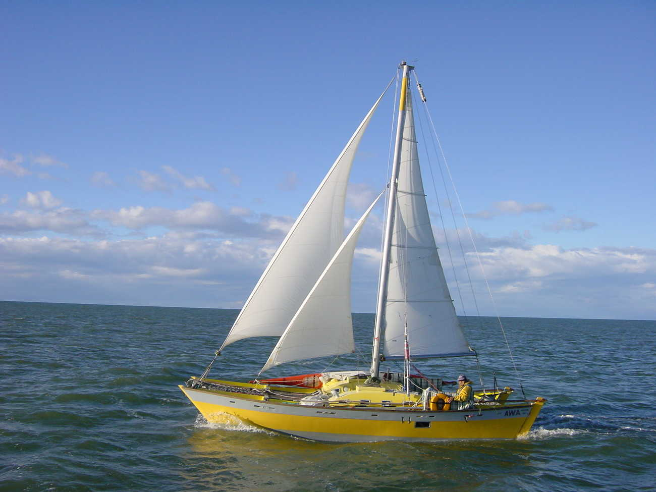 Yellow hulled Tanenui sailing out in the open, one man aboard