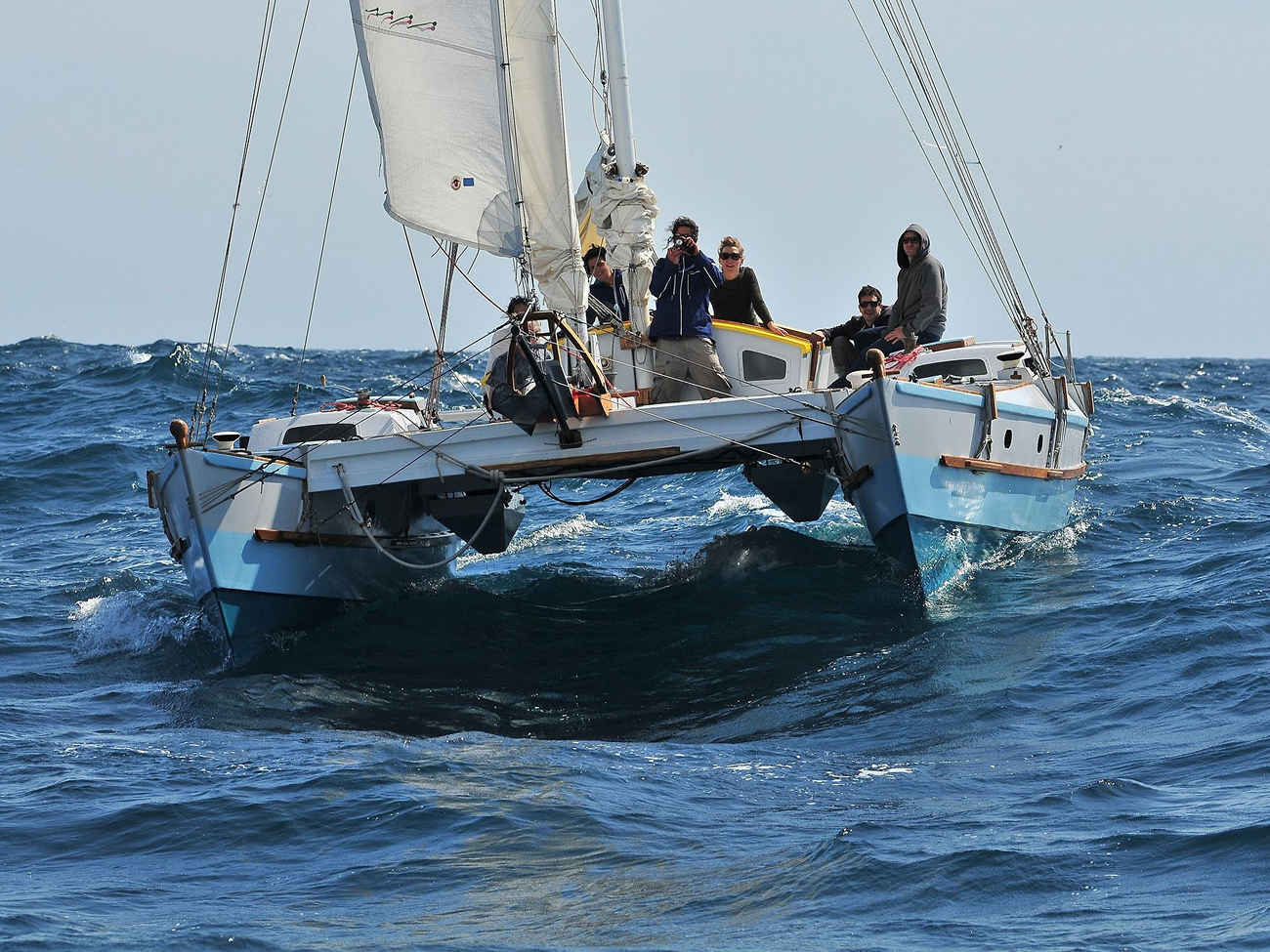 White and blue Tiki 38 sailing on choppy seas, six people aboard