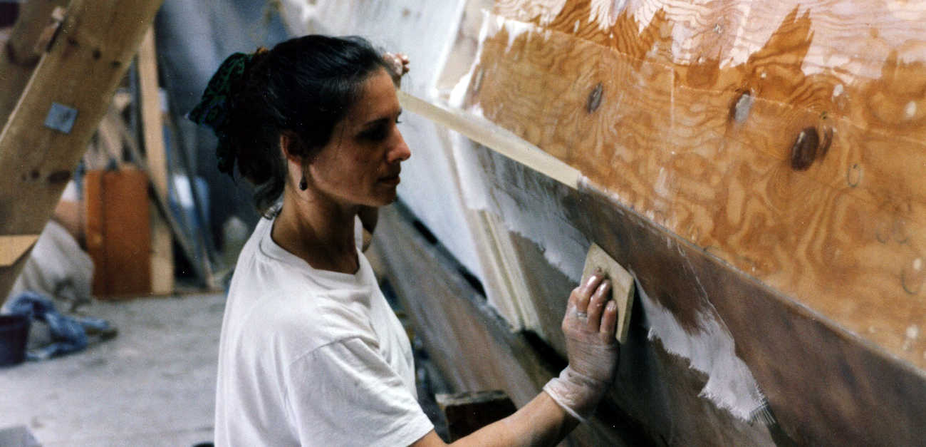 A helper working with glass cloth on a partially completed hull
