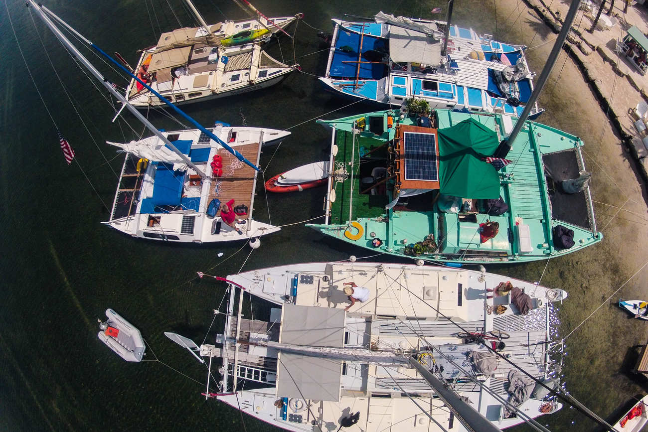 Aerial view of 5 colourful Wharram catamarans at the beach