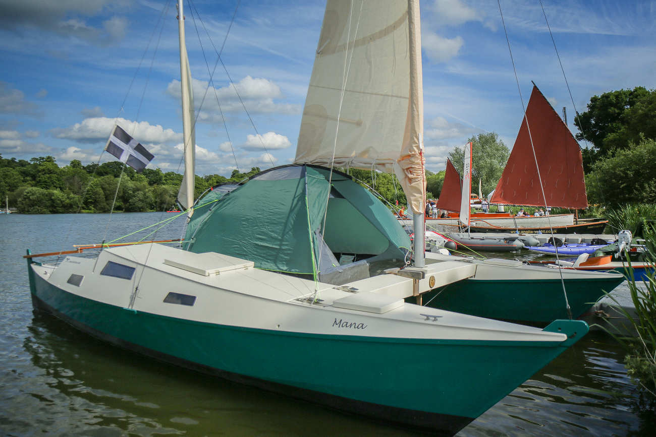 Wharram Mana 24 with white and teal hulls, with deck tent on board
