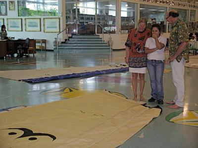 James, Hanneke and a third person looking at sails on the floor