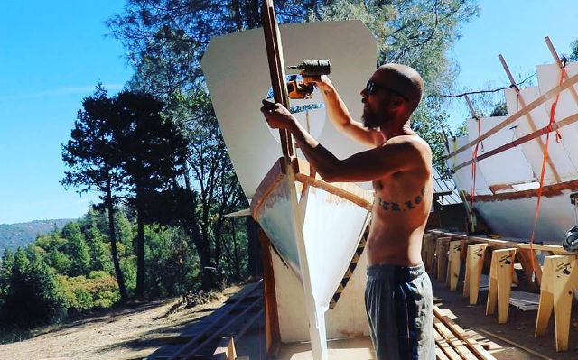 Builder using a power tool on a partially completed catamaran hull