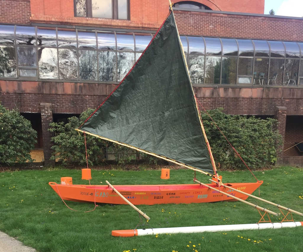 Orange outrigger canoe on the grass with green crabclaw sail up