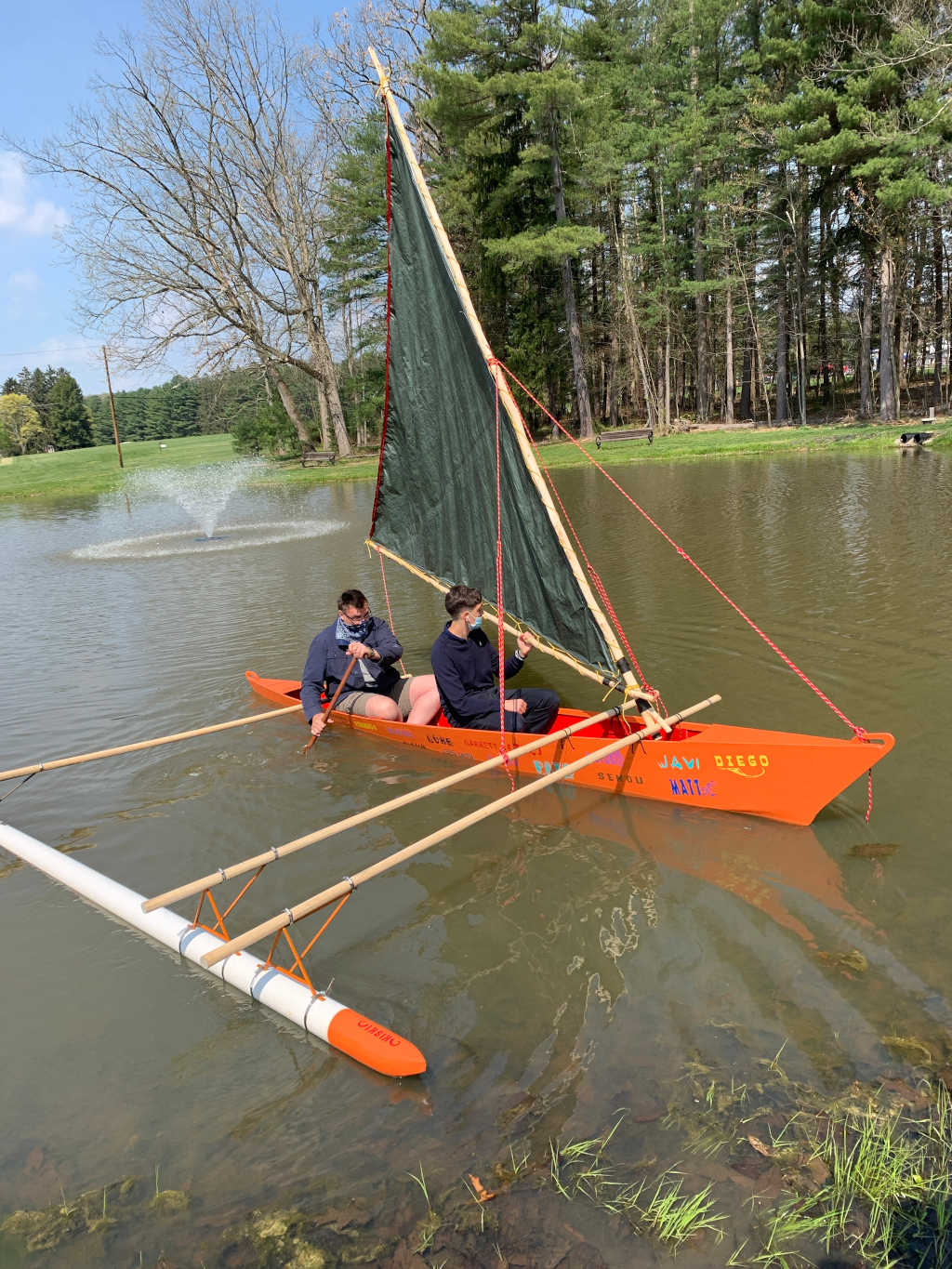 Outrigger canoe on the pond, crewed by two