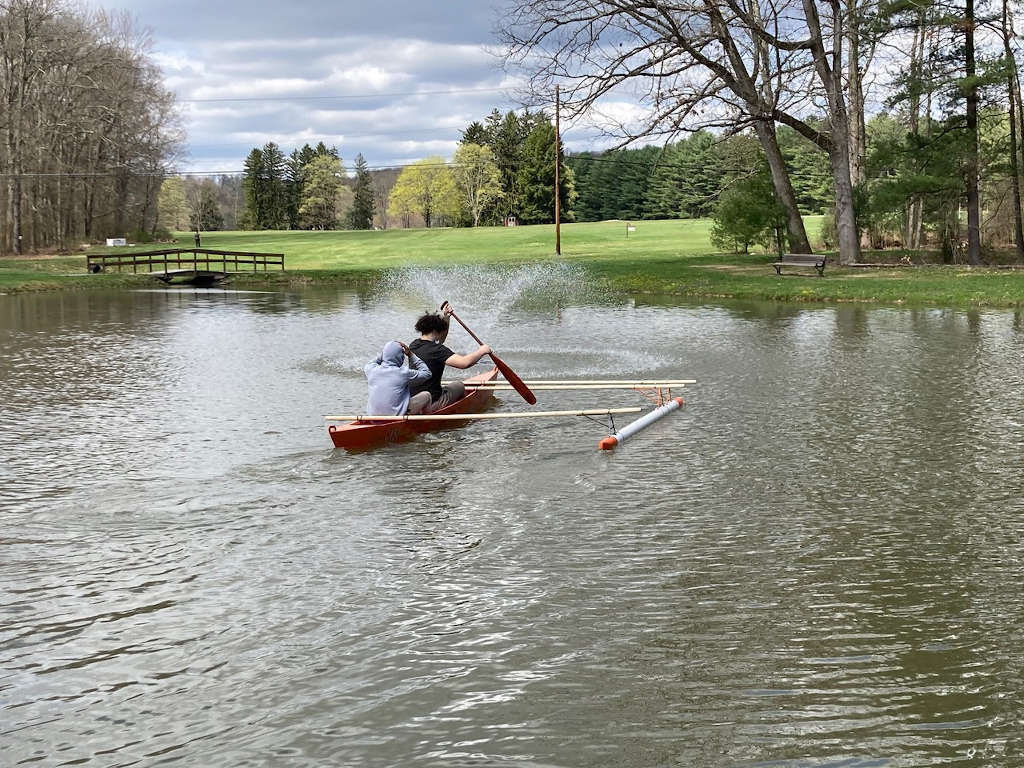 Outrigger canoe being paddled on the pond